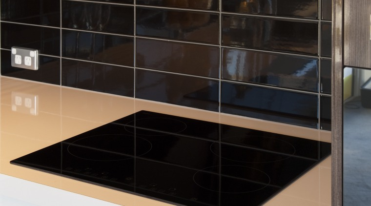 Black cooktop on white bench with black splashback. cabinetry, countertop, glass, kitchen, product design, black, white