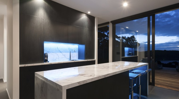 Entertainers kitchen with large waterfall bench-top and wood architecture, countertop, interior design, lighting, property, real estate, window, black, gray
