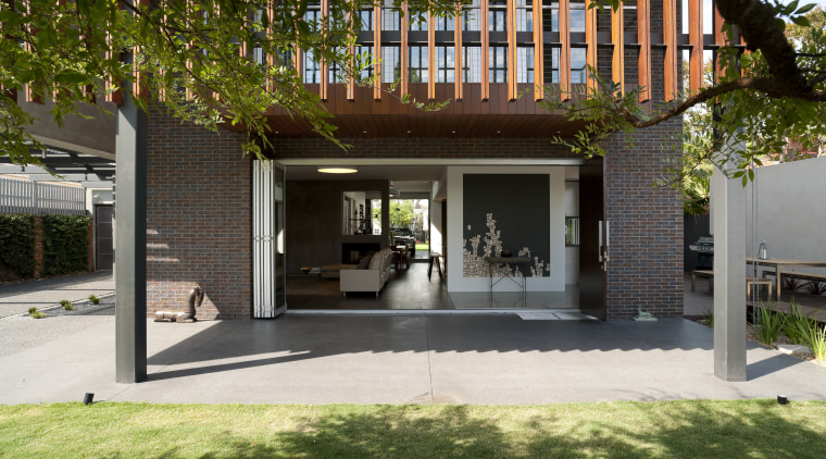 Large sliding doors open up the interior of architecture, backyard, courtyard, facade, home, house, outdoor structure, property, real estate, brown, black