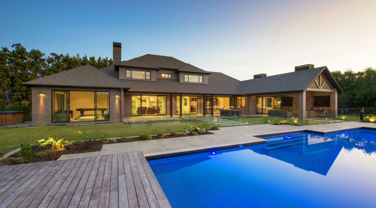 This contemporary, well-balanced masonry home was designed and backyard, cottage, estate, facade, home, house, leisure, mansion, property, real estate, residential area, resort, roof, swimming pool, villa, teal