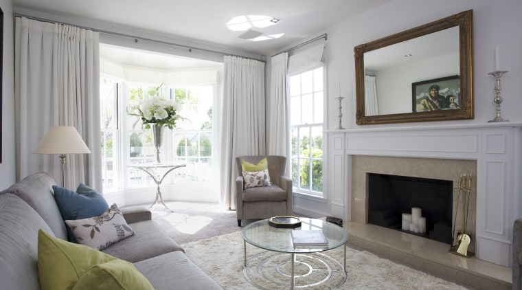 The front living room in this remodeled home ceiling, estate, floor, hearth, home, interior design, living room, property, real estate, room, wall, window, window covering, window treatment, gray