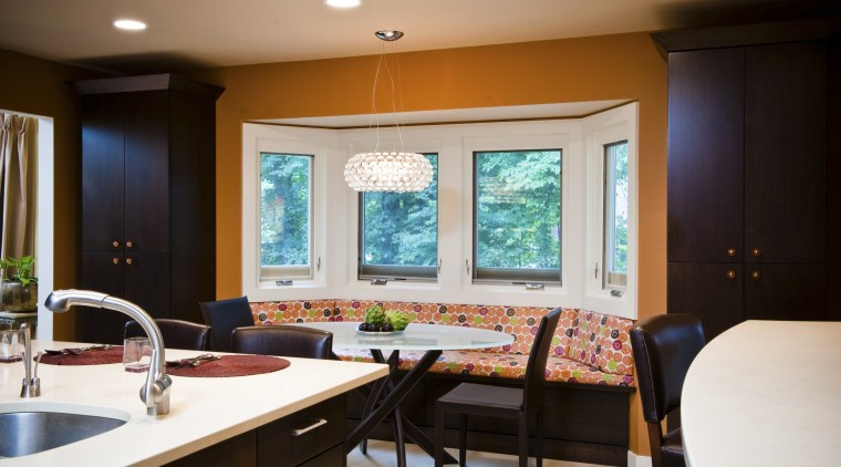 The reinvented banquette area in this kitchen has countertop, dining room, home, interior design, kitchen, room, table, window, black, white