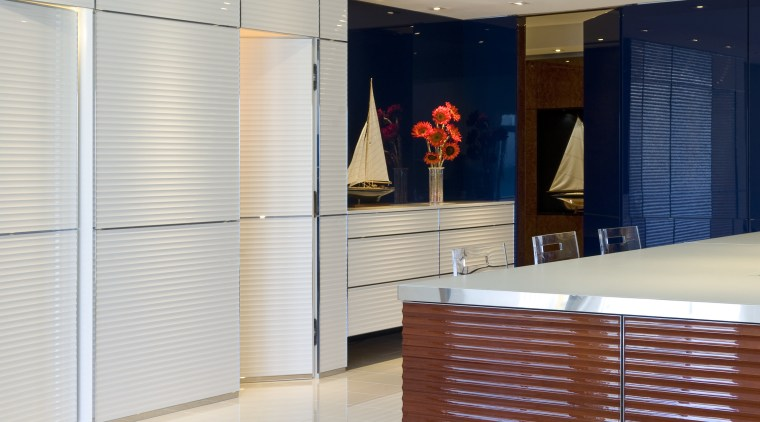 Walls conceal flush doors with touch openings in cabinetry, floor, flooring, furniture, interior design, lobby, room, wall, window blind, window covering, window treatment, gray