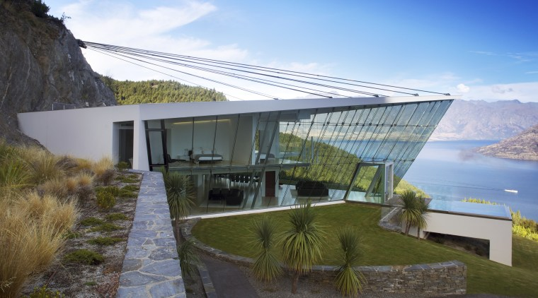 This glass-walled house, known as Jagged Edge, appears architecture, estate, house, property, real estate, sky, villa, water