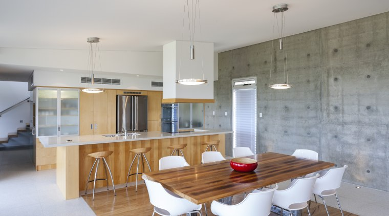 A raw concrete wall contrasts the warm wood architecture, countertop, dining room, house, interior design, kitchen, real estate, room, table, gray