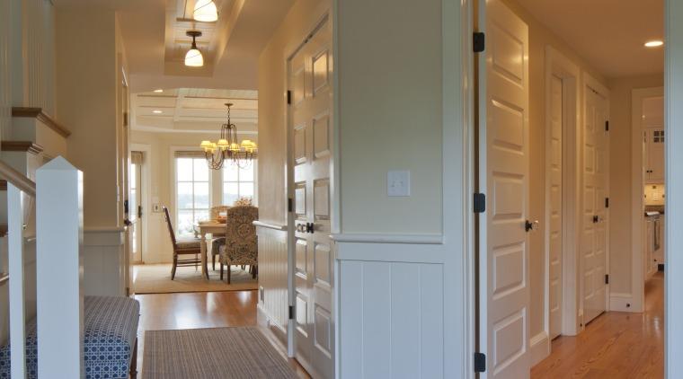 In this Cape Cod house, corridors lead off apartment, architecture, ceiling, daylighting, door, estate, floor, flooring, hardwood, home, house, interior design, laminate flooring, living room, lobby, real estate, room, wall, window, wood, wood flooring, gray, brown