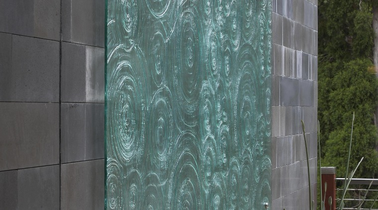 This slumped glass water feature is set against architecture, door, facade, glass, siding, wall, window, gray