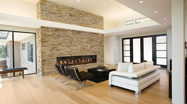 the natural stone wall appears to slice through ceiling, floor, flooring, hardwood, interior design, laminate flooring, living room, real estate, room, wall, wood, wood flooring, white