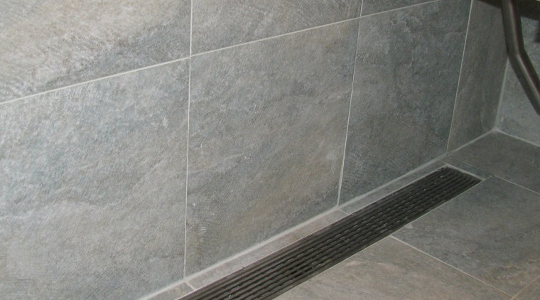 Luxe Linear Drain with a decorative steel grate. floor, flooring, plumbing fixture, tile, gray
