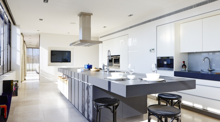 A cantilevered end to this 4.6m-long island forms countertop, interior design, kitchen, room, white