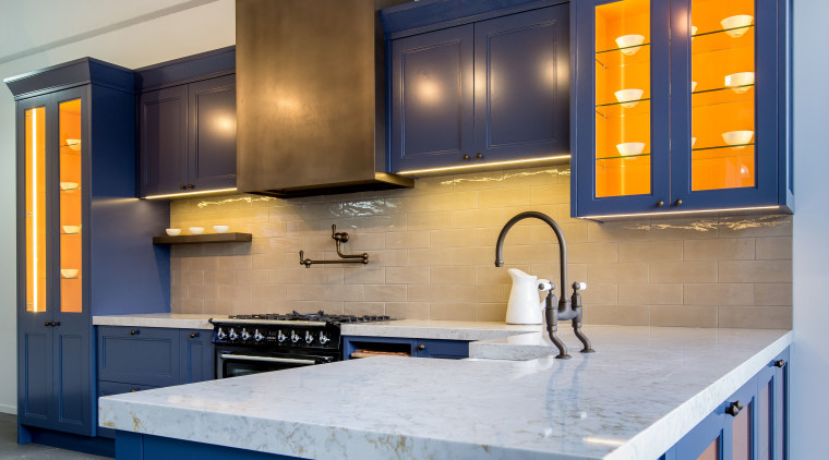White stone counters and blue cabinetry create a cabinetry, countertop, kitchen, room, gray