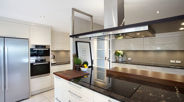 A removable wood prep board is integrated into countertop, cuisine classique, interior design, kitchen, real estate, white