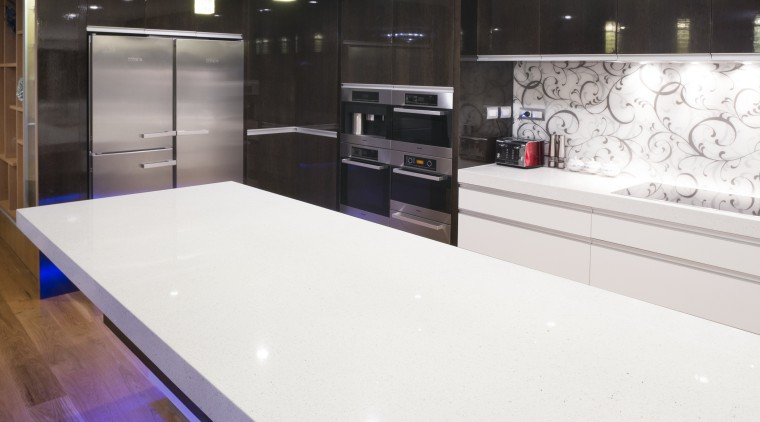 The 60mm-thick composite stone benchtop in this kitchen ceiling, countertop, floor, flooring, glass, interior design, kitchen, lighting, room, table, white