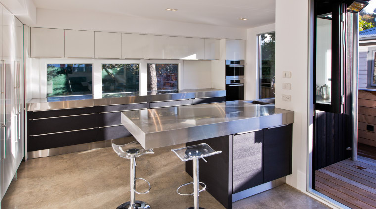This kitchen by designer Milvia Hannah responds to countertop, floor, interior design, kitchen, real estate, gray