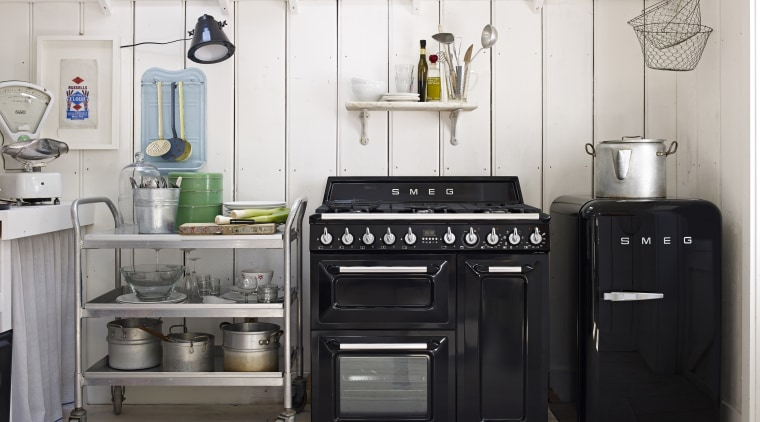 This pared-back kitchen highlights a return to a countertop, gas stove, home appliance, kitchen, kitchen appliance, kitchen stove, major appliance, refrigerator, room, small appliance, white, black