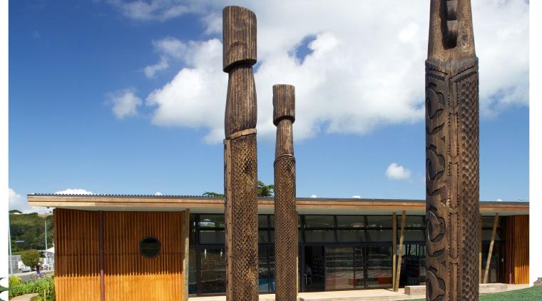Carved timber battens wrap around the exterior of cloud, column, grass, sky