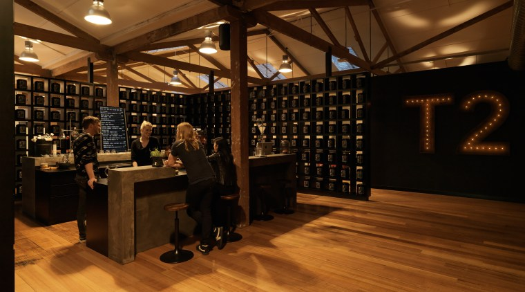 A former industrial warehouse in Melbourne is home floor, flooring, hardwood, interior design, liquor store, wood, wood flooring, brown, orange