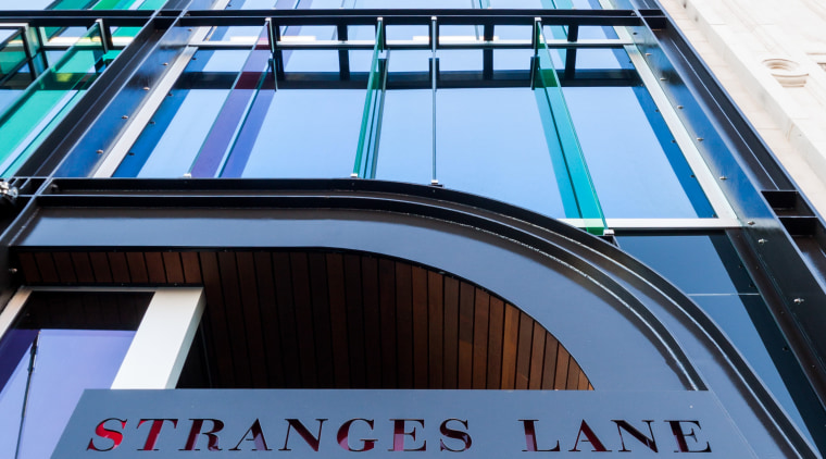 Close-up of STRANGES LANE sign  Above:Standing proud architecture, building, commercial building, daylighting, facade, line, metropolitan area, roof, sky, structure, urban area, black, white