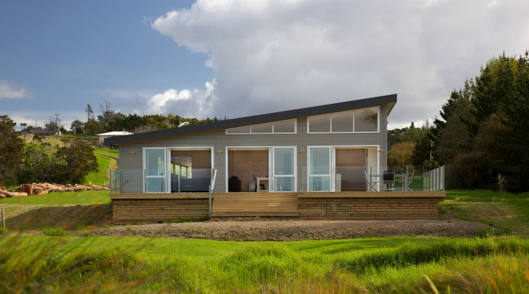 A soaring, monopitched roof allows space for clerestory architecture, cloud, cottage, elevation, estate, facade, farmhouse, grass, home, house, land lot, landscape, property, real estate, residential area, rural area, sky, villa, brown, gray