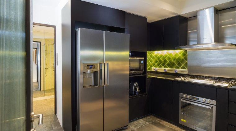 The kitchen in this renovated 1970s apartment features cabinetry, countertop, home appliance, interior design, kitchen, major appliance, real estate, refrigerator, black