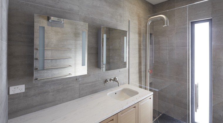 In this bathroom design by Rachel Barnes, the bathroom, countertop, floor, home, interior design, real estate, room, sink, gray