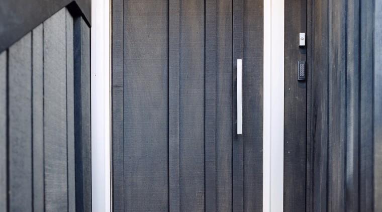 This custom architectural front door melds into the door, floor, hardwood, home, house, wall, window, wood, wood stain, black, gray