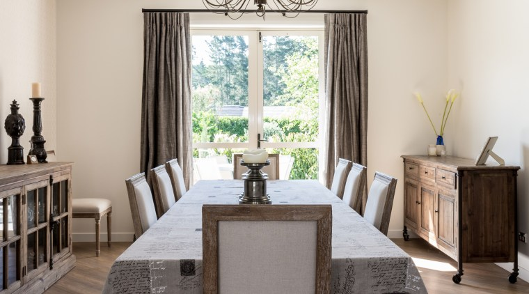 Full drapes frame the view from the dining ceiling, chair, dining room, floor, flooring, furniture, home, interior design, living room, room, table, white