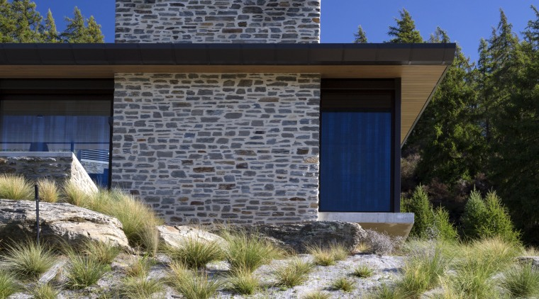 On this alpine home, the material palette has architecture, cottage, elevation, estate, facade, grass, grass family, home, house, land lot, landscape, landscaping, property, real estate, residential area, sky, blue, brown