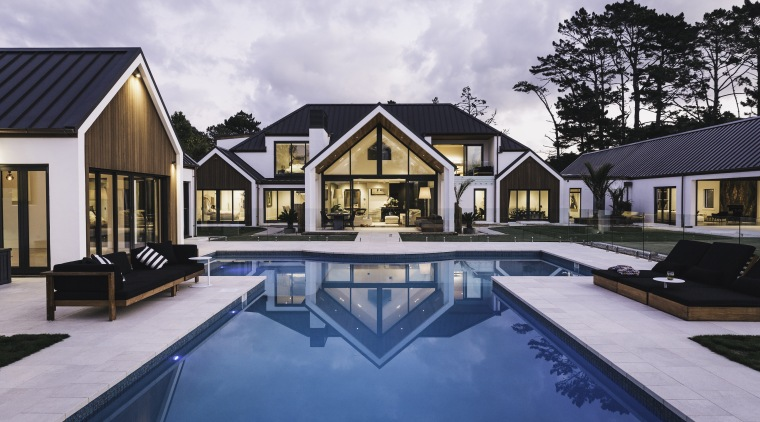 Strong, symmetrical gable forms combined with bold white cottage, estate, home, house, leisure, property, real estate, reflection, residential area, resort, swimming pool, villa, water, white