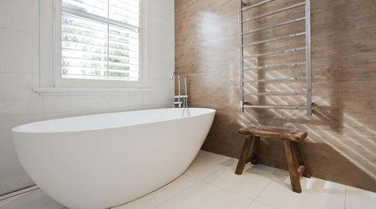 A freestanding tub adds to the sense of bathroom, floor, flooring, interior design, plumbing fixture, product design, property, room, tap, tile, gray
