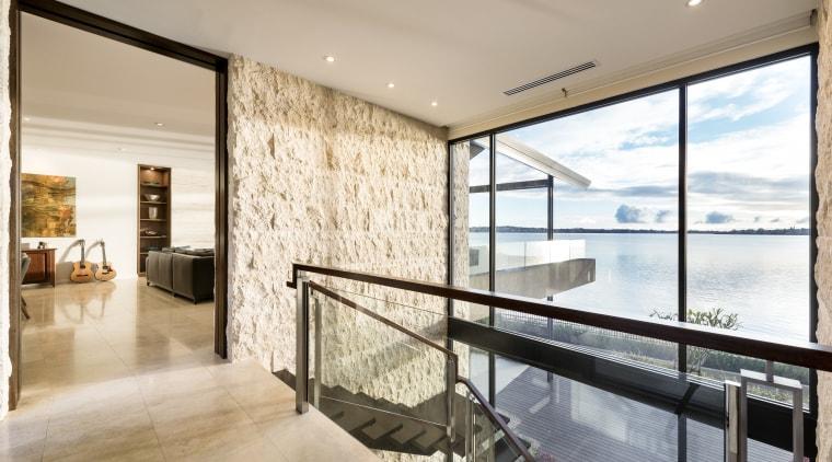 Stone exteriors wrap around to form interior walls apartment, architecture, condominium, estate, home, house, interior design, living room, penthouse apartment, property, real estate, window, gray