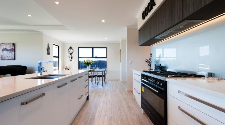 A substantial range and modern glass splashbacks make countertop, interior design, kitchen, real estate, room, gray