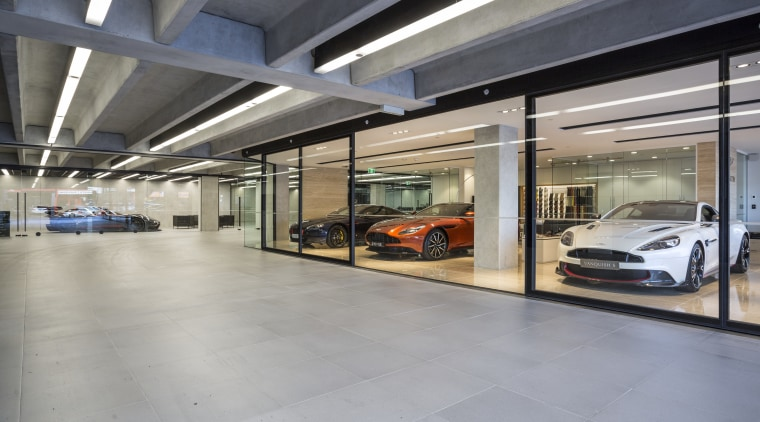 Large-format, matt concrete pavers provide a unifying refined automotive design, car, car dealership, executive car, garage, luxury vehicle, motor vehicle, parking, gray