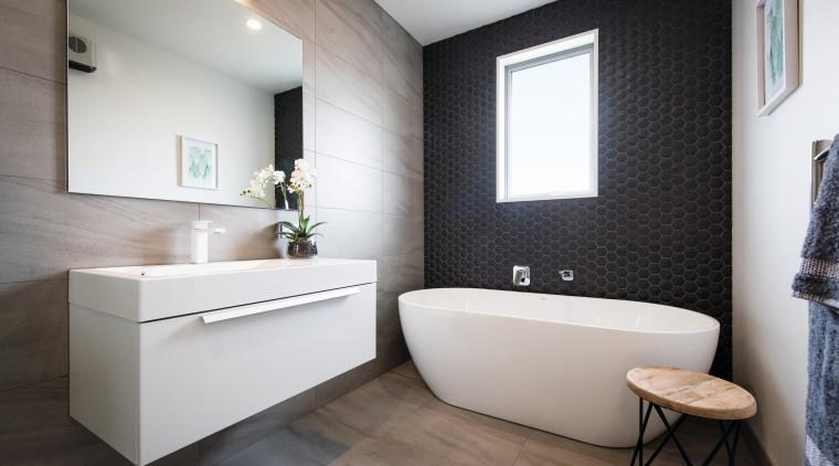 This contemporary GJ Gardner-designed bathroom includes a hexagon bathroom, floor, home, interior design, product design, room, sink, gray, black