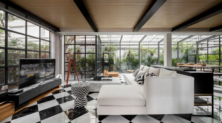 An expansive downstairs living space was transformed beyond architecture, house, interior design, living room, real estate, window, gray, black