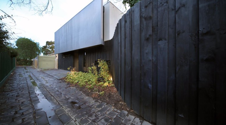 This home's hidden entry echoes the fencing along architecture, building, facade, home, house, property, real estate, residential area, sky, tree, wall, black