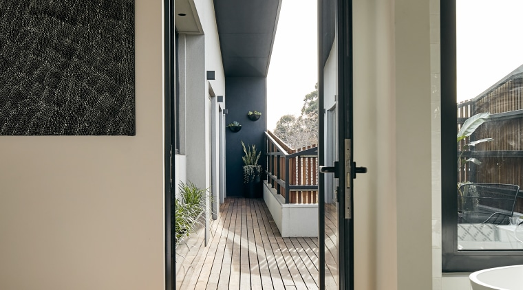 Expansive decks are a feature of this two-storey apartment, architecture, black-and-white, building, ceiling, daylighting, design, door, floor, flooring, furniture, hall, home, home door, house, interior design, line, loft, property, real estate, room, stairs, wall, window, white, gray, brown