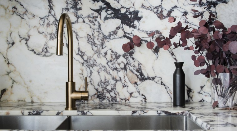 The dark cabinetry connects with the dark veining