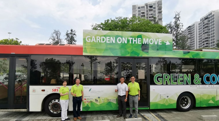 """The Singapore green-roofed 10-bus initiative is called """"Gardens advertising, architecture, bus, car, commercial vehicle, mode of transport, motor vehicle, tour bus service, tourism, transport, tree, vehicle, gray, black, white"""