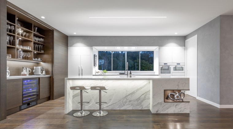 A solid bank of cabinetry and appliances is architecture, building, cabinetry, ceiling, countertop, daylighting, design, floor, flooring, furniture, hardwood, home, house, interior design, kitchen, lighting, living room, material property, property, room, shelf, shelving, table, tile, wall, window, wood flooring, gray