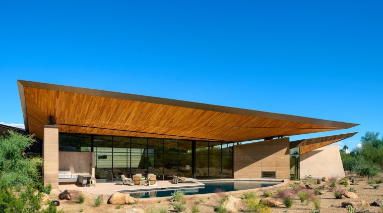 The large form of the roof hangs overhead architecture, home, house, real estate, roof, teal, brown