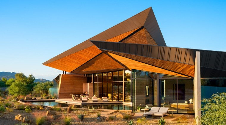 The home rises out of the desert like architecture, cottage, farmhouse, home, house, real estate, roof, sky, teal, brown