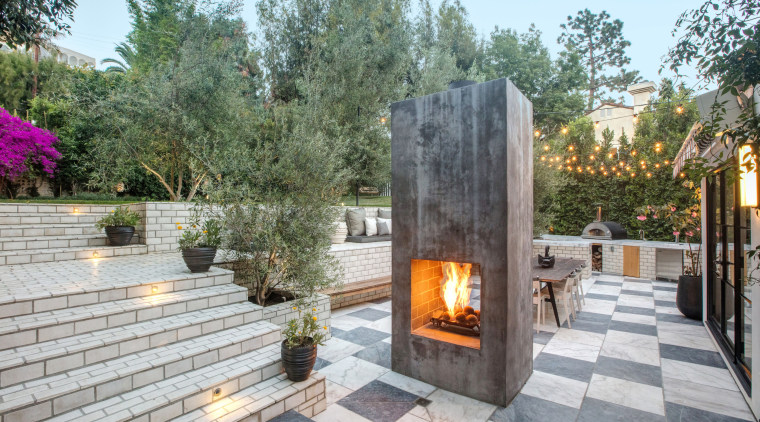 The back patio and outdoor fireplace. - To