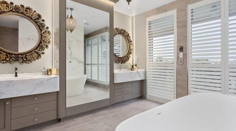 This luxury bathroom by designer Mark Bruce boasts bathroom, bathroom accessory, bathroom cabinet, estate, floor, flooring, home, interior design, room, window, gray