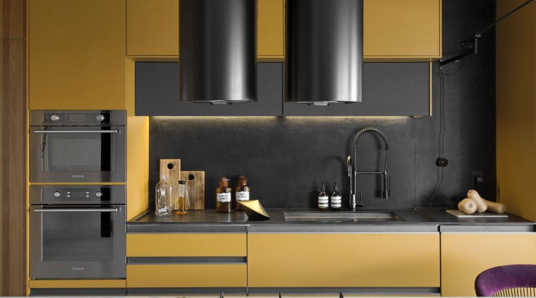 The custom-designed rangehoods provide a dramatic feature in cabinetry, countertop, cupboard, exhaust hood, floor, flooring, furniture, gloss, home appliance, interior design, kitchen, kitchen appliance, kitchen stove, material property, property, room, small appliance, tile, yellow, black, brown