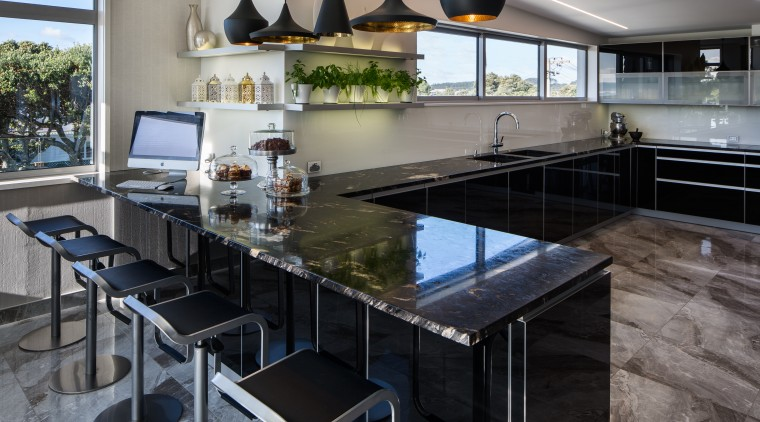 The large seating area acts as a servery countertop, interior design, kitchen, real estate, gray, black