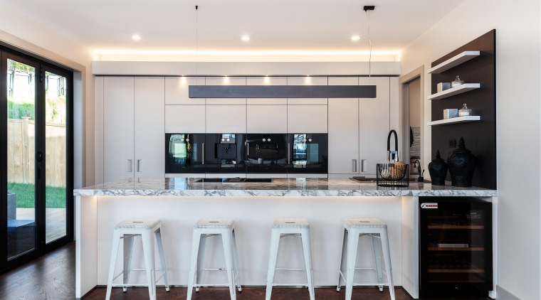 The kitchen is a gathering point in this cabinetry, countertop, cuisine classique, interior design, kitchen, white kitchen,  Gaggenau, Chancellor Construction, parquet floor, Arclinea kitchen, marble benchtop