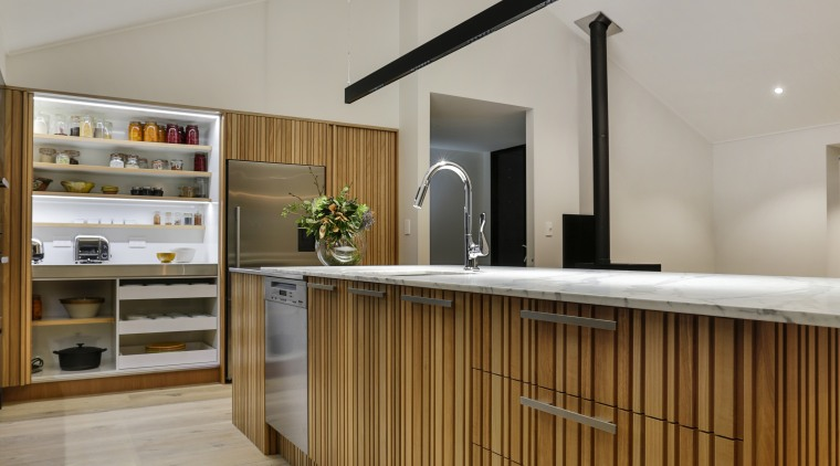 Side cabinetry wall in this kitchen features distinctive architecture, ceiling, daylighting, floor, flooring, furniture, interior design, lobby, wood, gray, brown