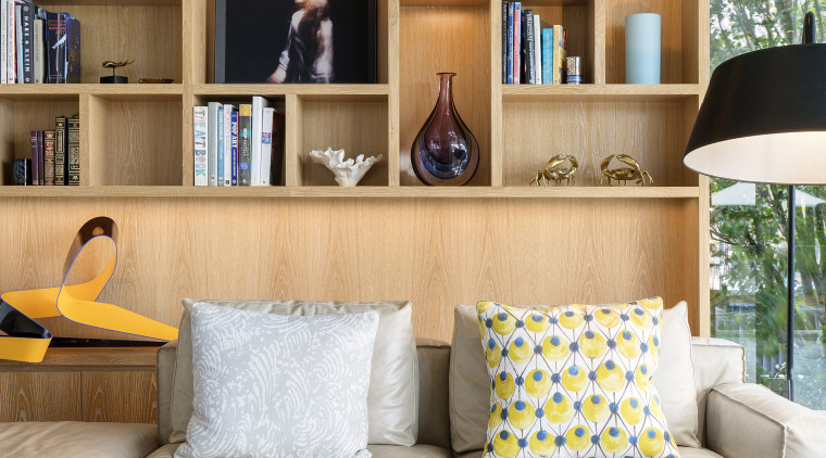 ​​​​​​​This family living area in front of the bookcase, couch, furniture, home, interior design, living room, room, shelf, shelving, table, wall, white, SAOTA