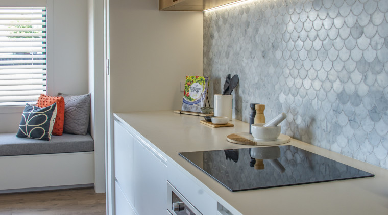​​​​​​​An attractive sheeny splashback is a feature of apartment, architecture, building, cabinetry, ceiling, countertop, floor, flooring, furniture, home, house, interior design, kitchen, material property, property, real estate, room, sink, tile, wall, yellow, gray